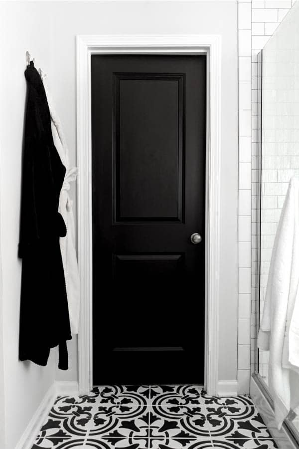 black painted door in black and white bathroom with painted tile