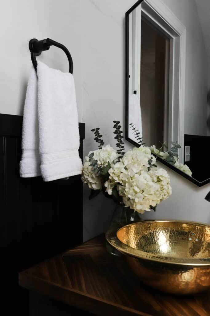 black and white powder room with gold accents