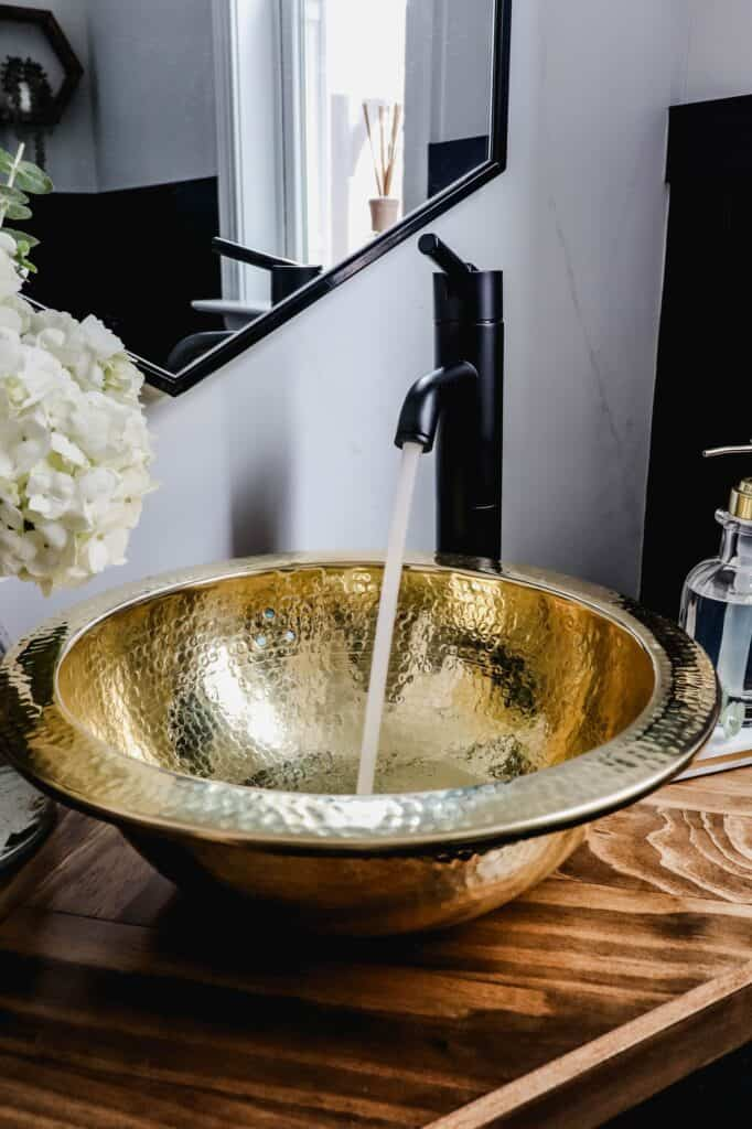 gold vessel sink with black Pfister Contempra faucet