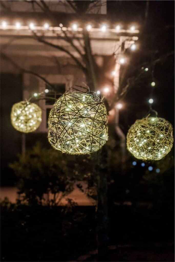 twine light balls shining outside and hanging from a tree
