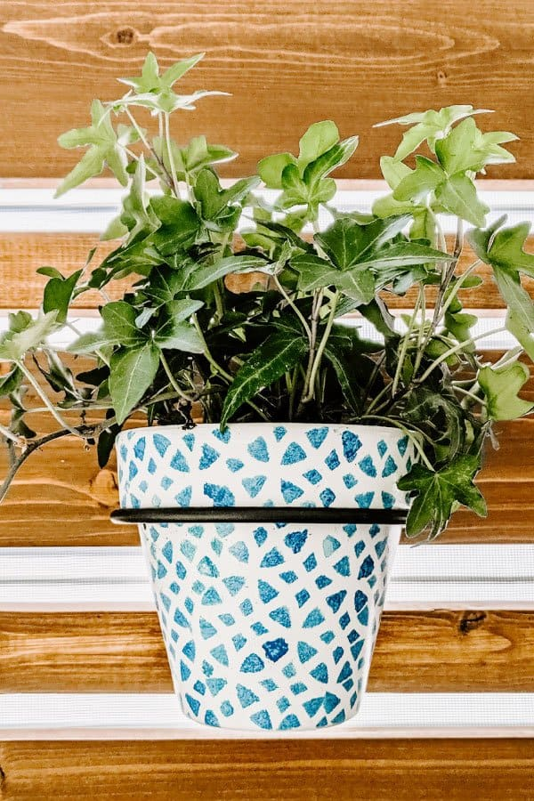 close-up of painted pot hanging on privacy planter wall