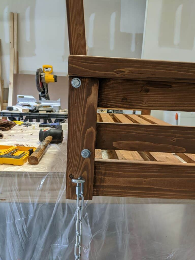 Adding hardware to the side of the DIY porch swing so that you can hang it up