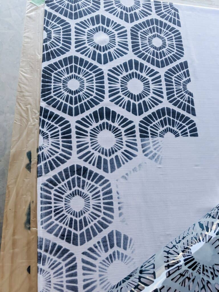 Removing stencil from curtain to reveal the pattern