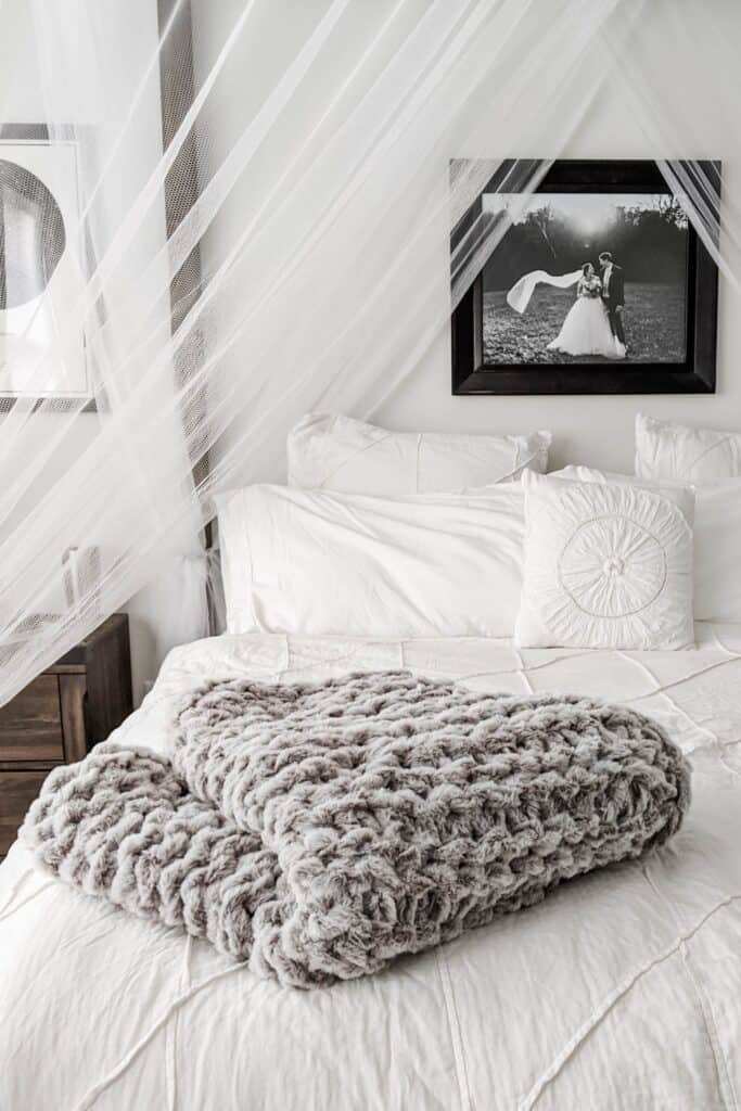 knit blanket folded on canopy bed with white bedding