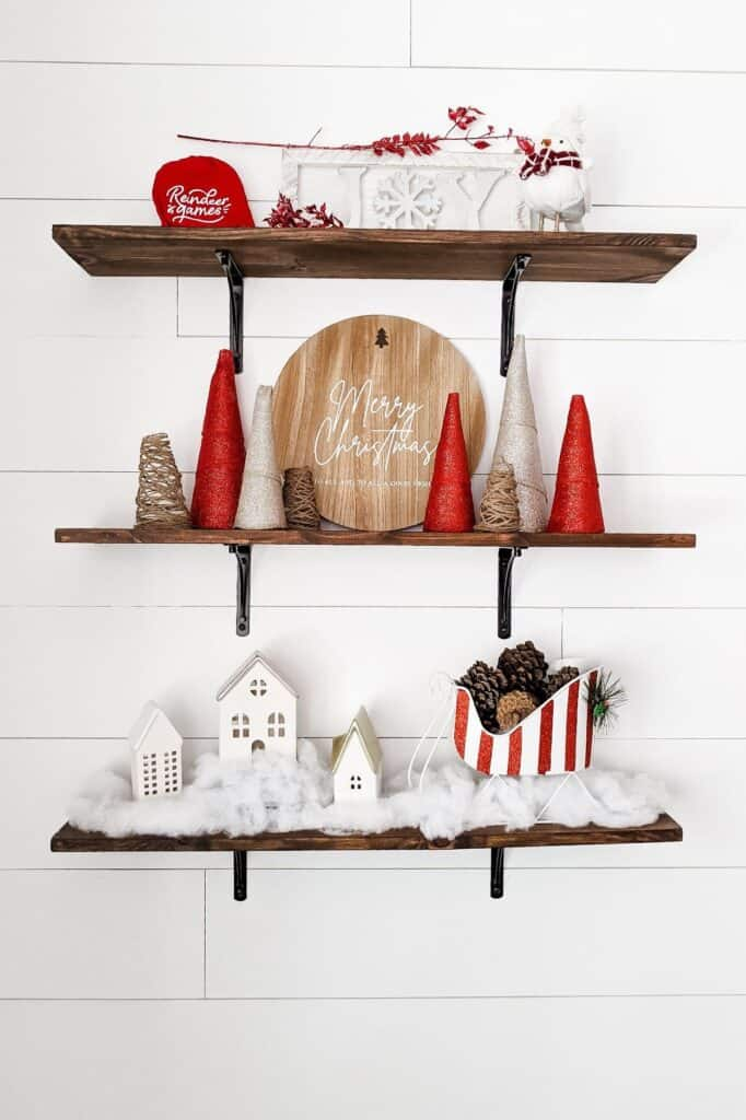 Wood shelves styled with red and white Christmas decor and twine trees
