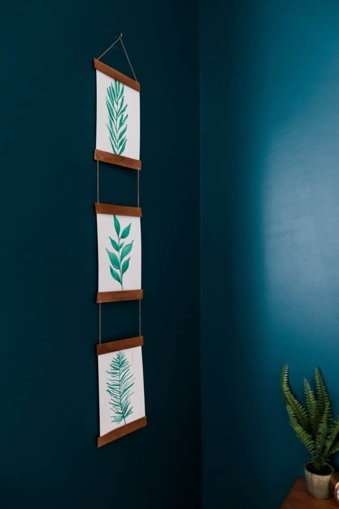 wood photo hanger with leaf artwork on dark blue wall