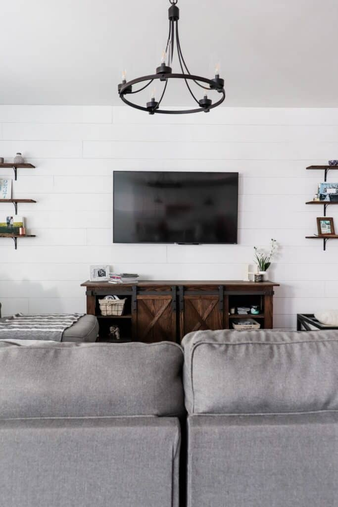 farmhouse living room with shiplap wall and oak tv console with sliding barn doors