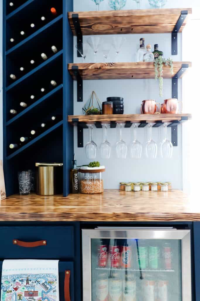 navy dry bar with wood shelves, countertop, and slanted wine rack