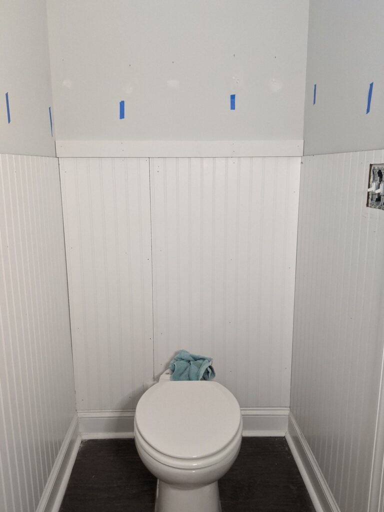 hanging white beadboard in powder room