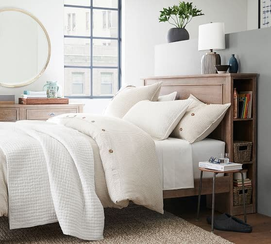 Pottery Barn bed with storage on side of wood headboard