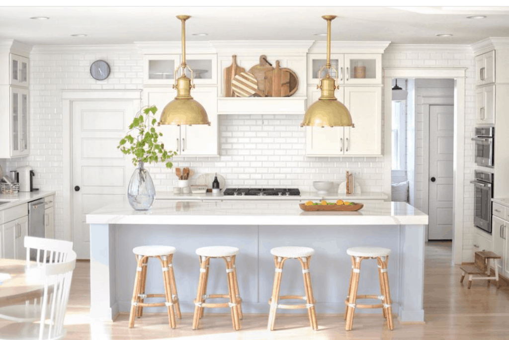 white kitchen with big gold pendant lights and light blue island