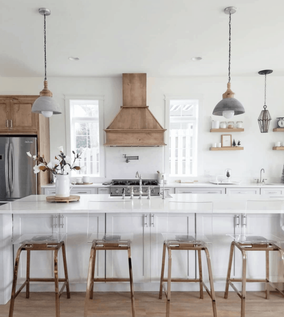 white kitchen with wood vent hood and concrete pendent lights