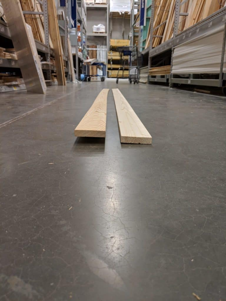 bowed and warped pine board on floor of home improvement store next to straight pine board