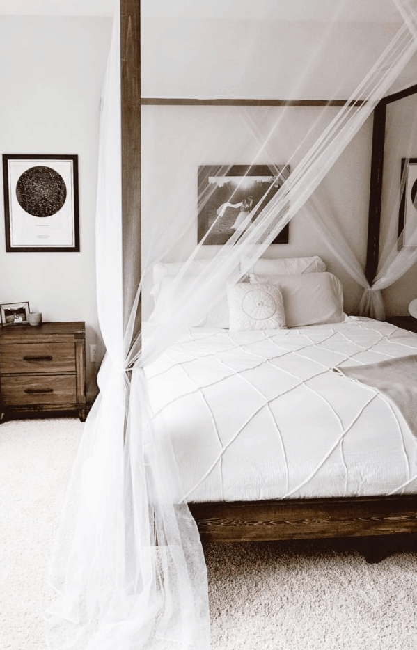 DIY wood canopy bed with netting and white bedding