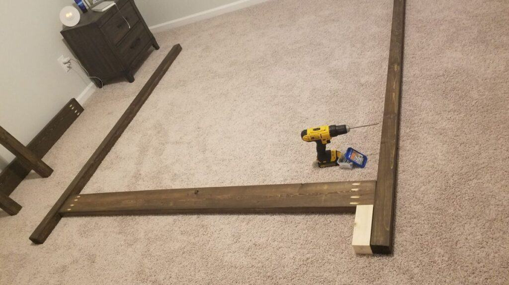 assembling side rails of DIY canopy bed with a drill