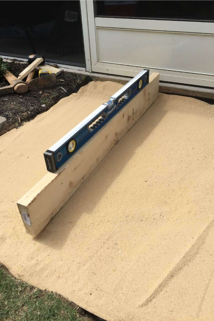 leveling sand using a 2x4 and level