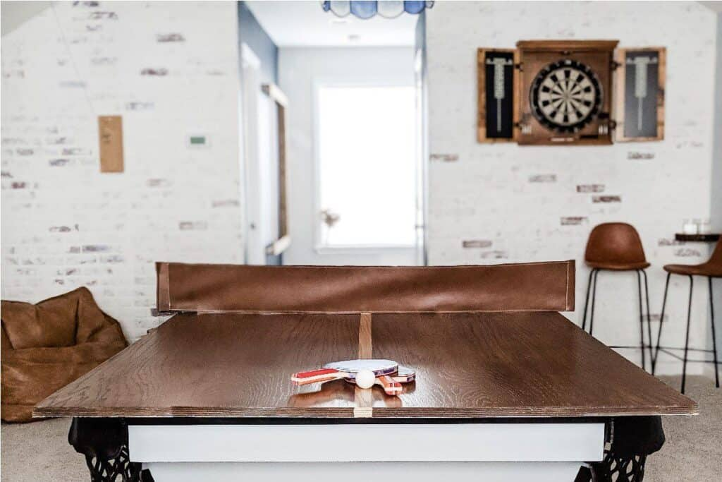 Wood ping pong table topper with leather net in game room