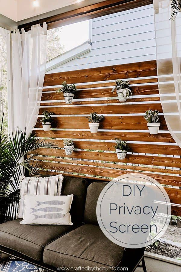 DIY privacy wall on screened in porch with hanging terracotta pots and plants