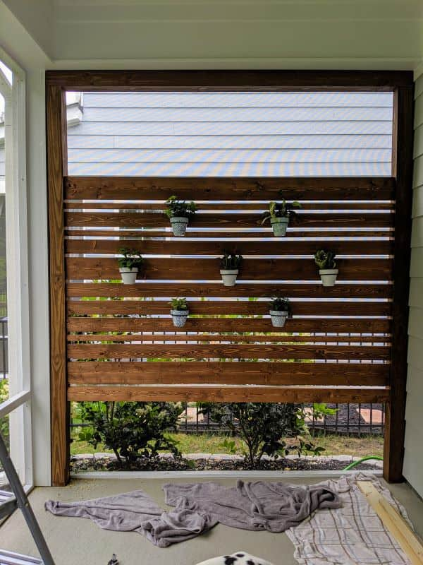 patio privacy wall with hanging plants in pots
