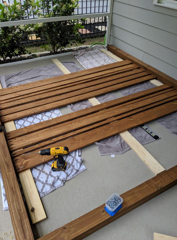 screwing in wood slats to create privacy screen with different sized boards