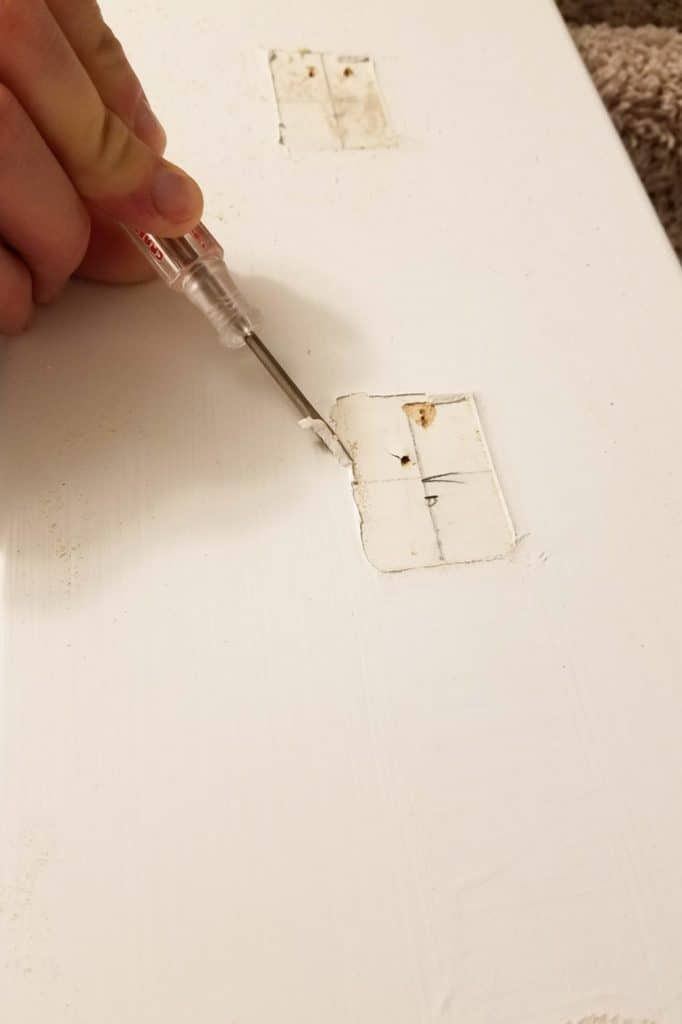 scraping paint using a screwdriver