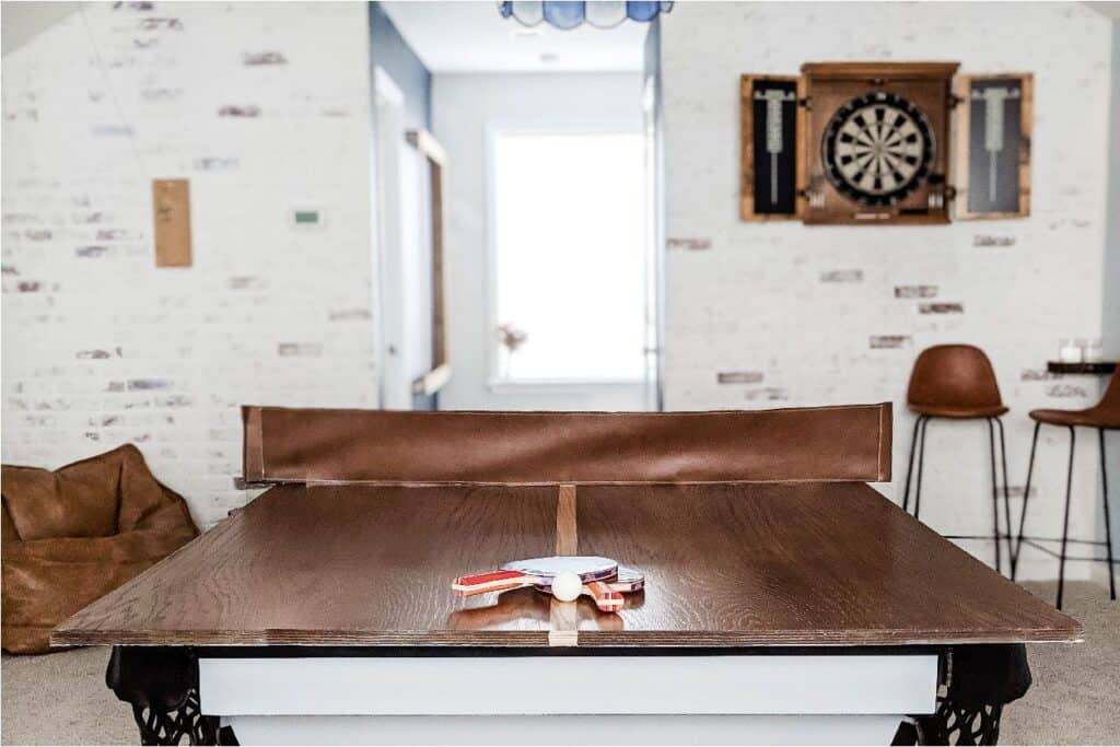 DIY wood ping pong table with leather net in game room
