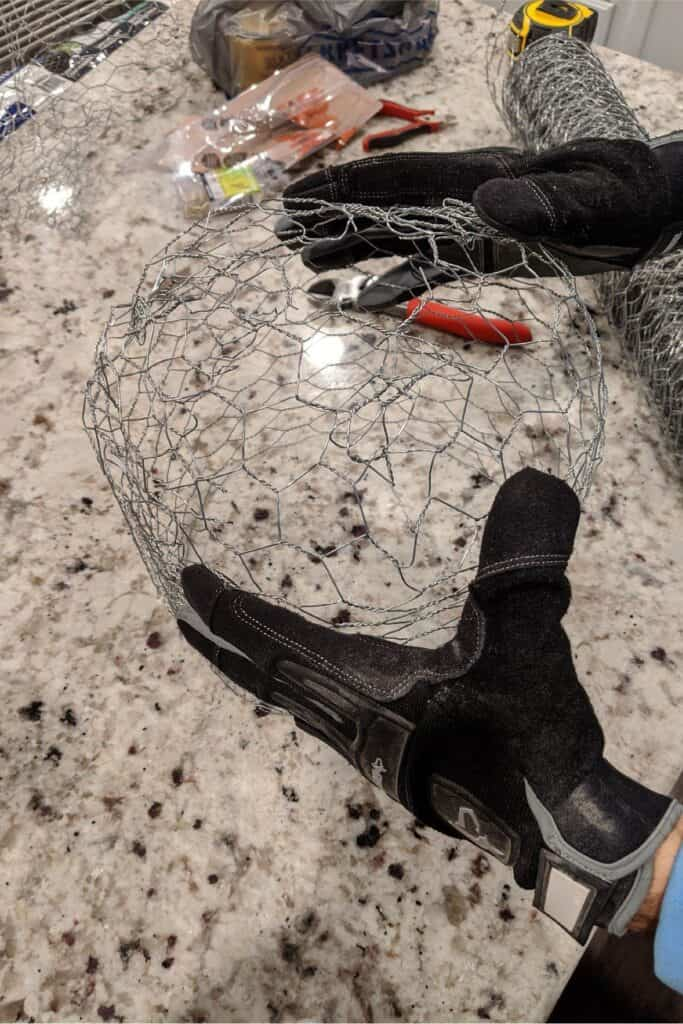 forming chicken wire into a ball while wearing gloves