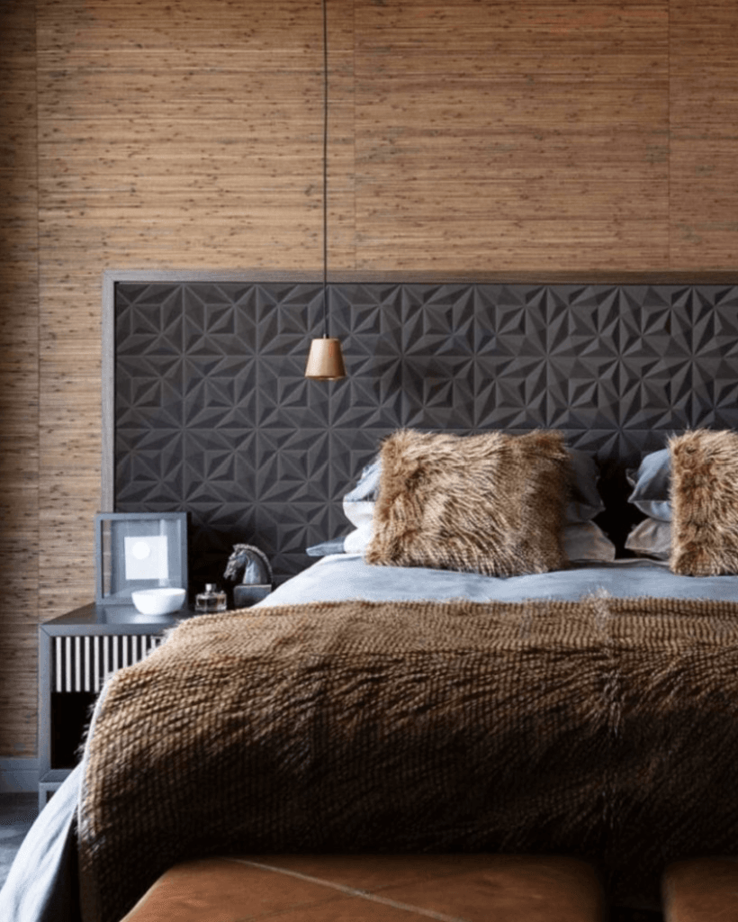 dark, textured wall paper headboard behind bed with fur pillows