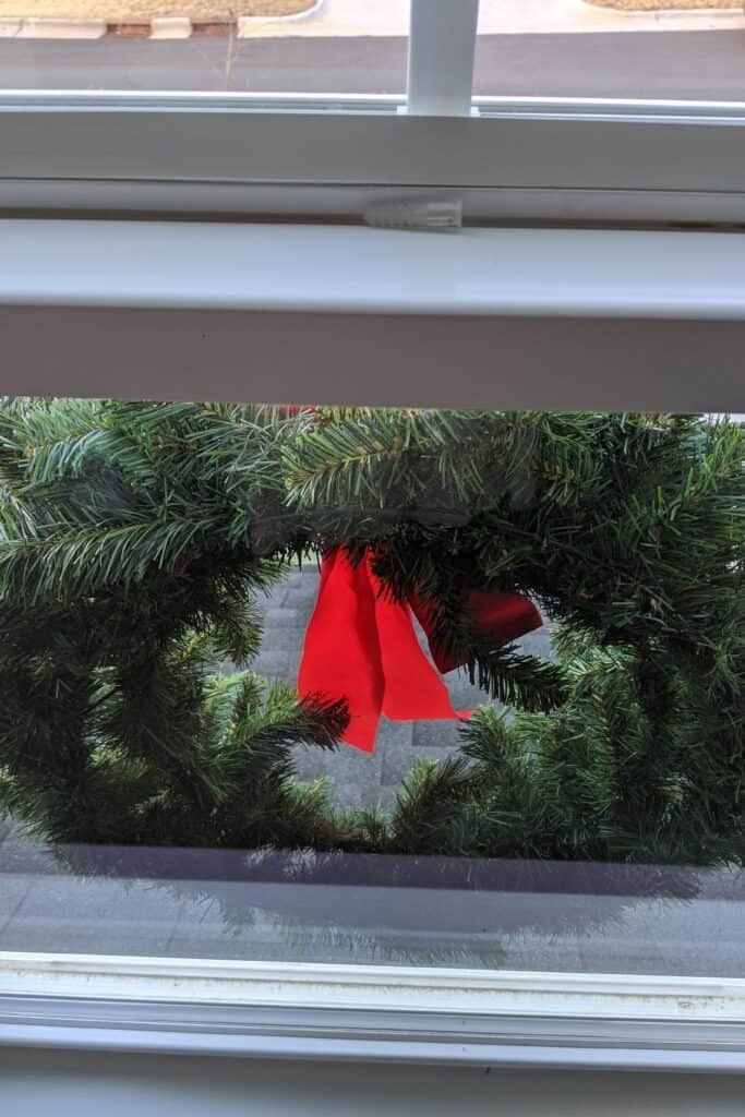 wreath with bow hanging on exterior window with drywall anchor - view from inside