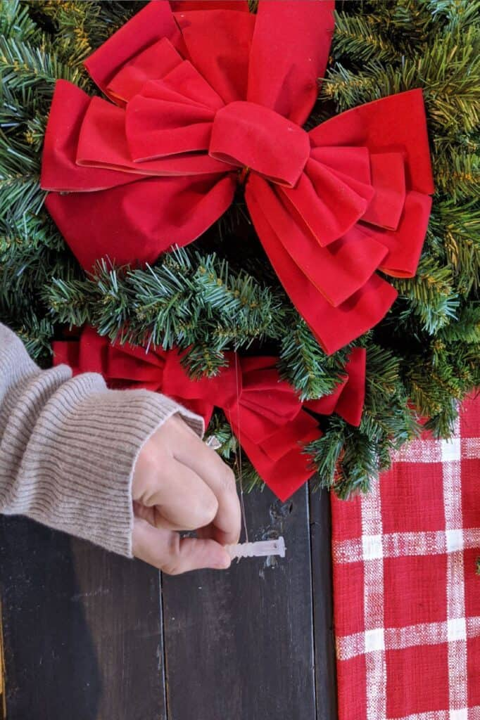attaching fishing line and drywall anchor to wreath