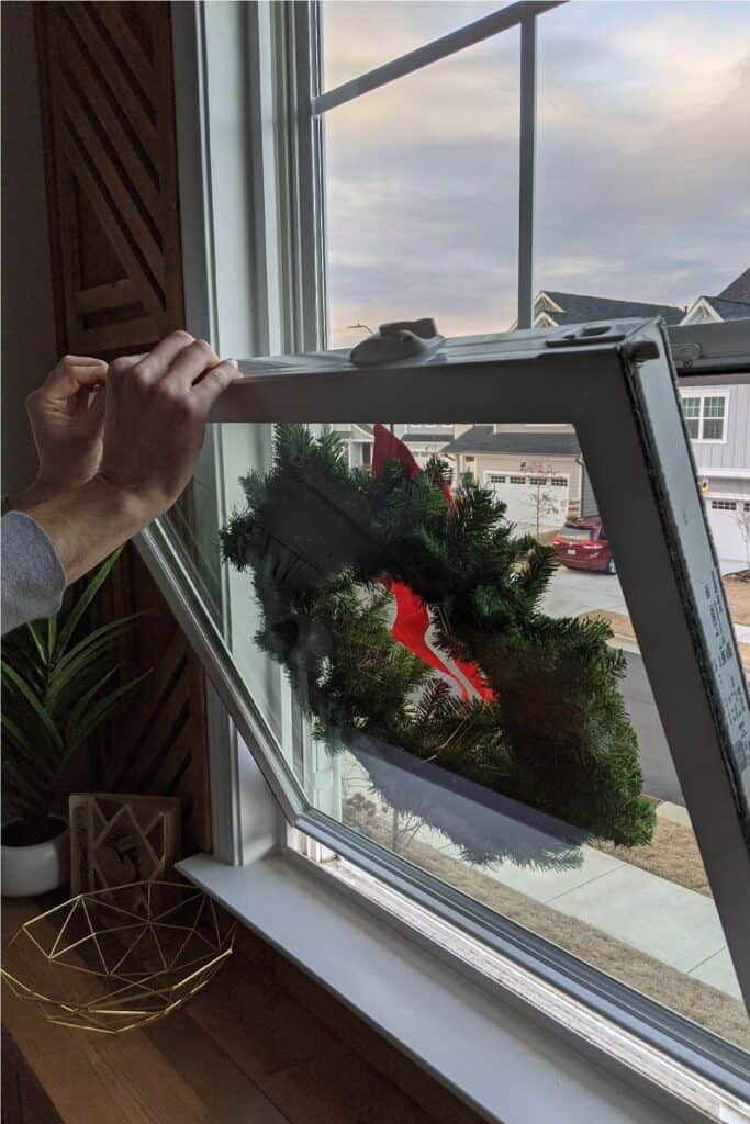 hanging Christmas wreath on exterior window from inside of house