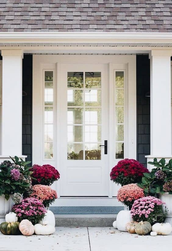 front porch with pink flowers and pumpkins
