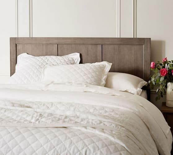 Simple wood headboard with white sheets