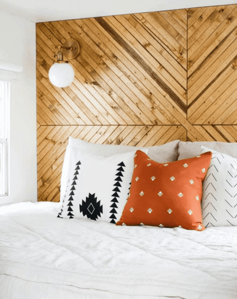 geometric wood accent wall behind white bed