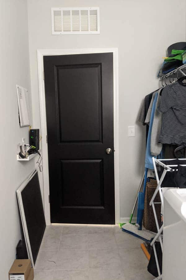 black door in messy laundry rom