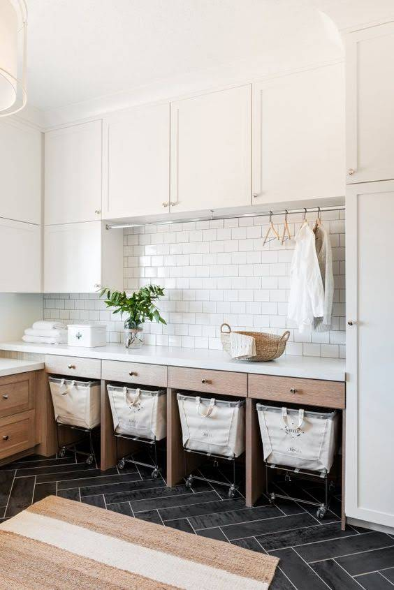 laundry room with white cabinets and clothes rod, black herringbone floor, and laundry carts