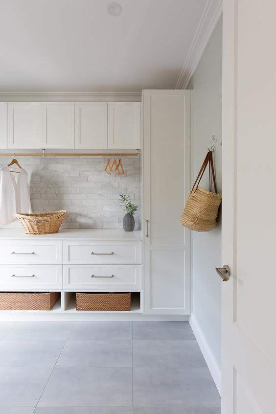 white laundry room with clothes rack and storage