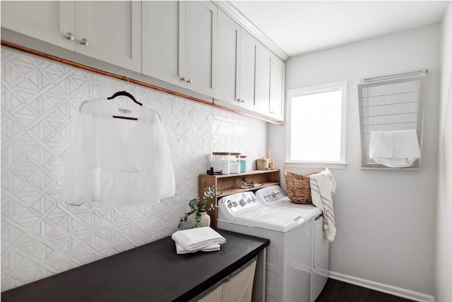 bright laundry room with white backsplash, Sherwin Williams Repose Gray cabinets, and shelf above washer dryer