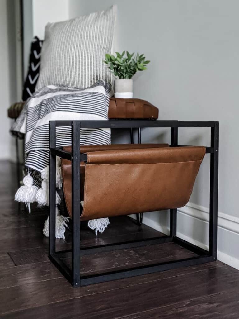 leather magazine rack with modern wood frame sitting in entryway