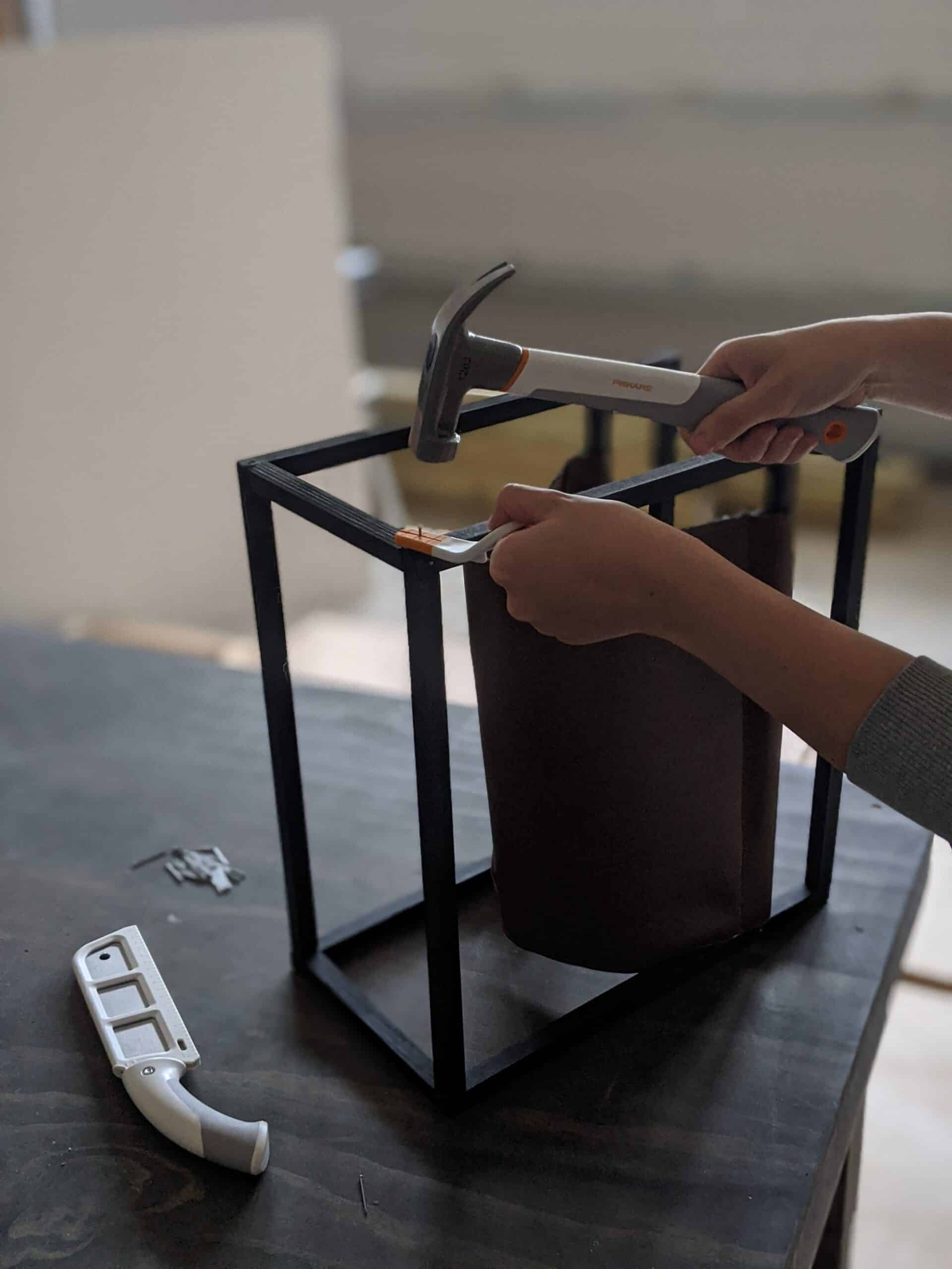 assembling leather magazine holder using nails and hammer