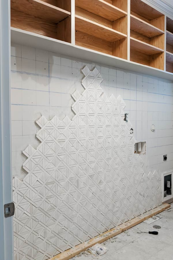 tiling up wall with mosaic tiles