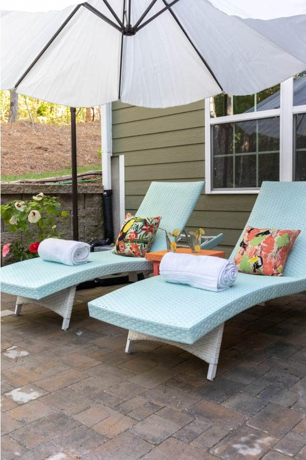 blue outdoor chaise lounge chairs with tropical pillows