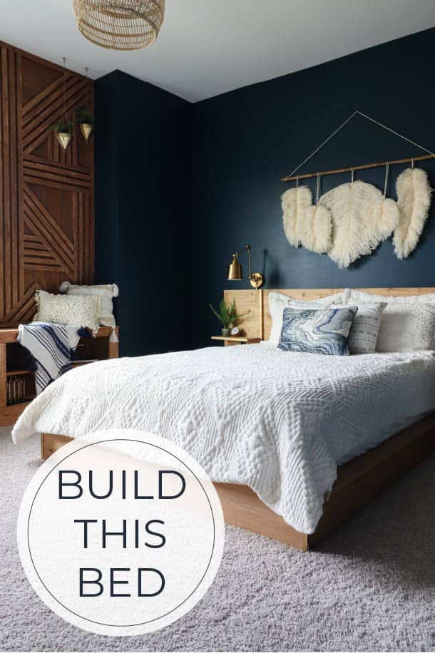 wood platform bed in bedroom with dark blue and wood walls