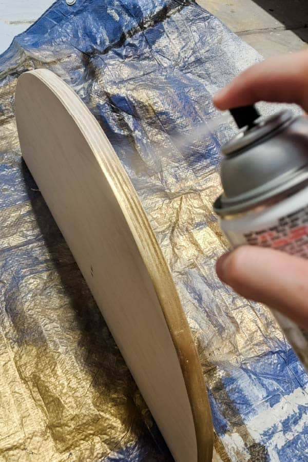 spray painting plywood half circle edge with gold paint