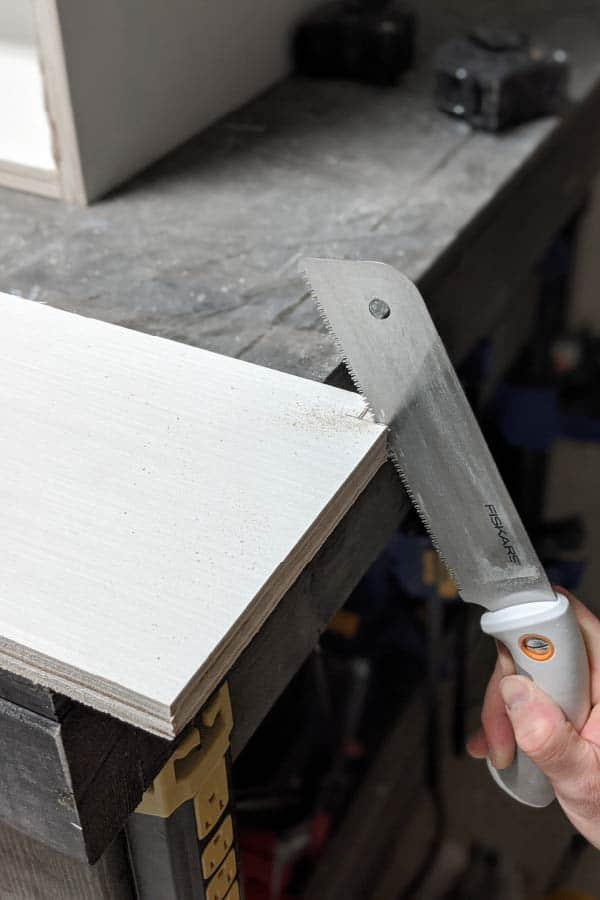 cutting corner out of shelves using hand saw