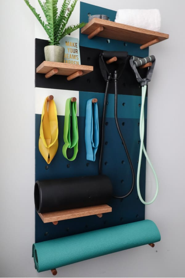 Pegboard holding gym equipment