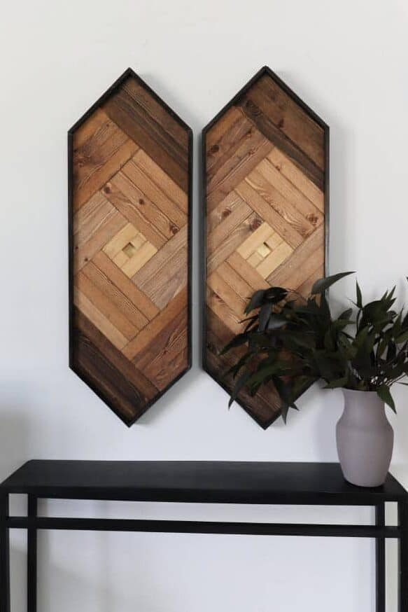 Geometric wood wall art in long hexagon shape hanging above narrow table