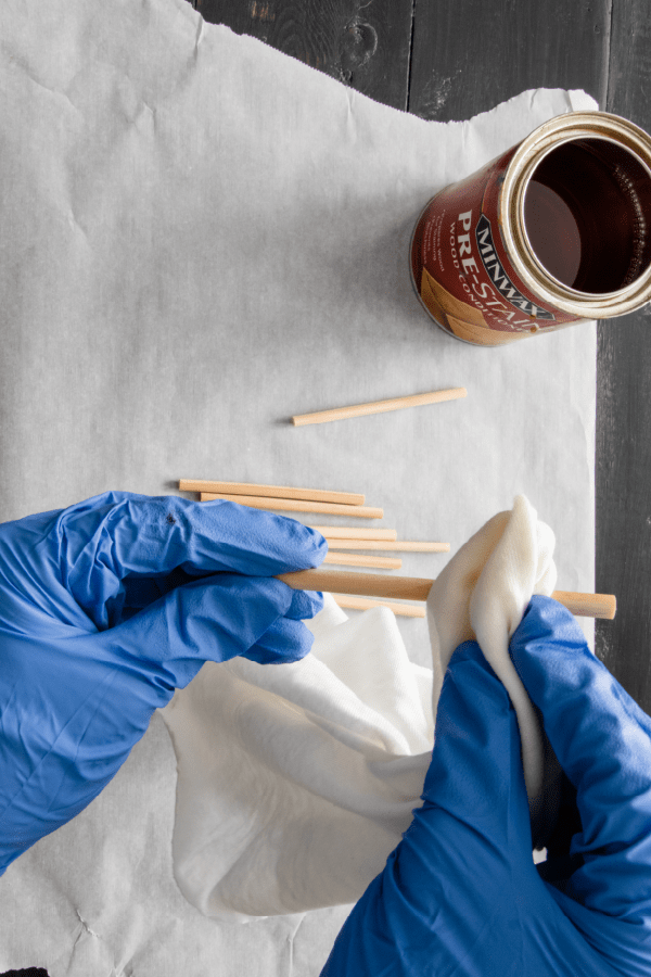 Applying pre-stain to wood dowels using a rag