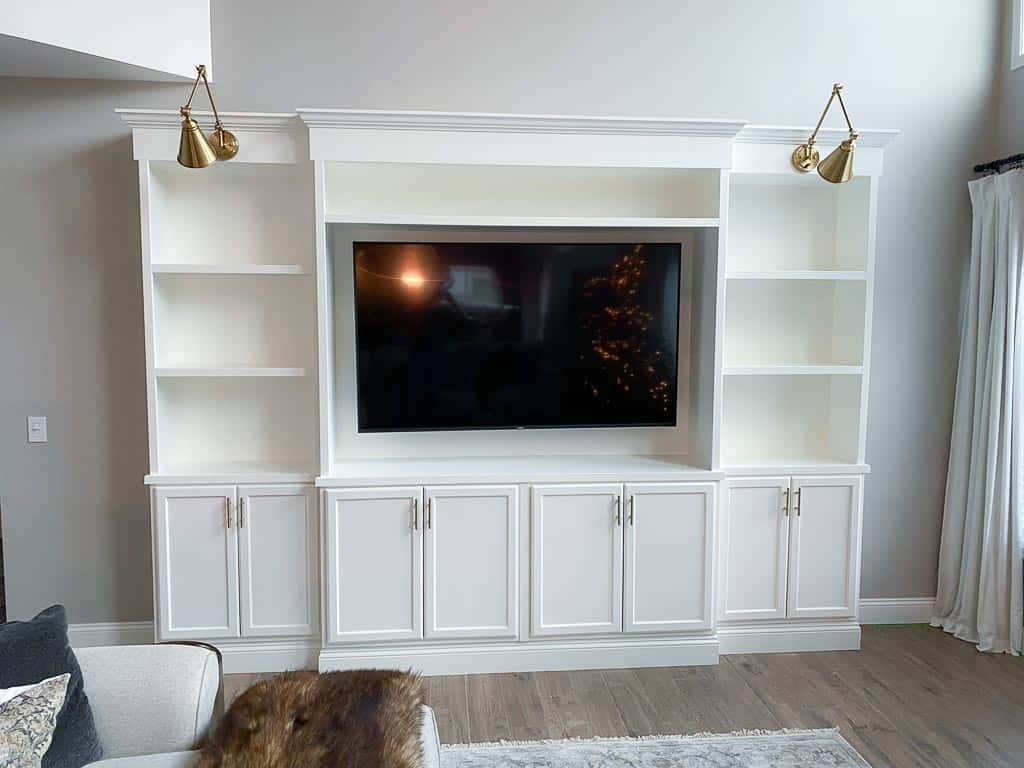 white built-in entertainment center with gold sconces