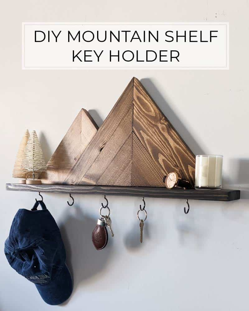 DIY mountain shelf key holder with small decor, a hat, and keys hanging from it